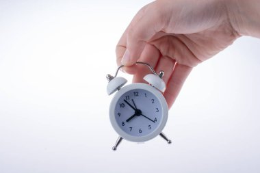 Alarm clock in hand on a white background