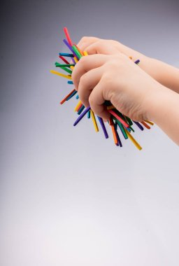 Hand letting coloured wooden  sticks fall on white background