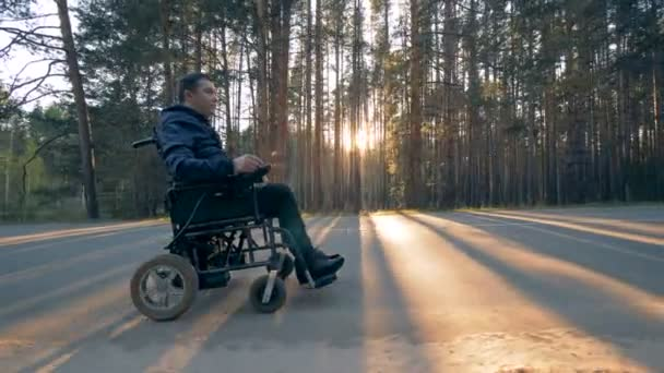 Behinderte fährt im Rollstuhl auf der Straße.