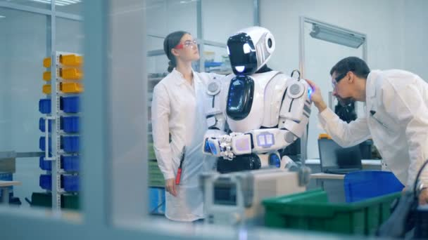 Two professionals are inspecting a robotic humanoid