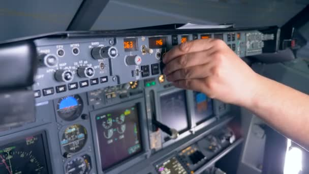 Multiple buttons on a planes console are being pushed and rotated by a pilot