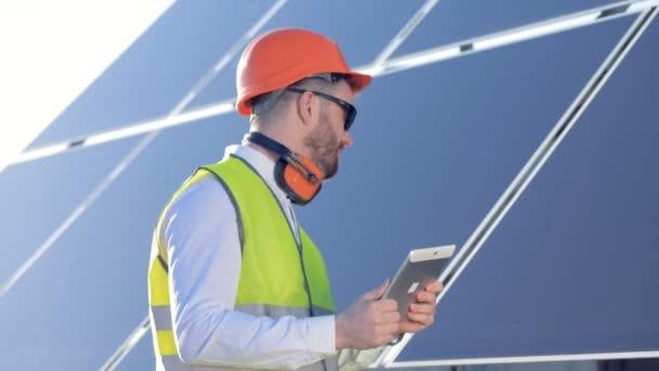 Profesionální stojící poblíž solární panel a práci s jeho tabletový počítač