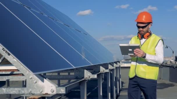 Solární panely je stále kontrolována mužský expert na pracovní oděvy
