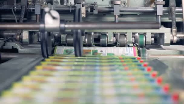 New books go off a printing machine, moving on an assembly line.