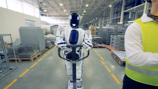 Human-like robot is pulling a factory transporter while walking together with a factory worker