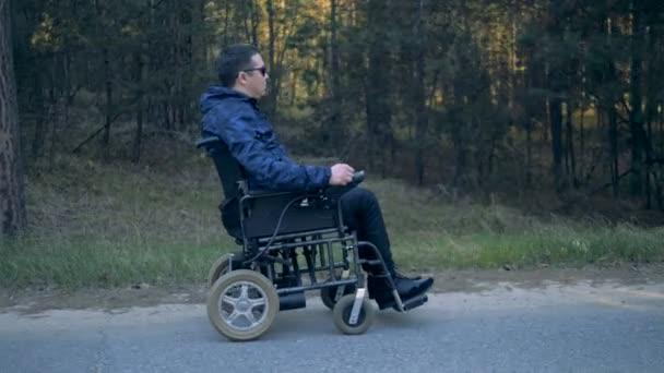 Boční pohled na postižené muže pohybující se po silnici v jeho powered invalidní vozík