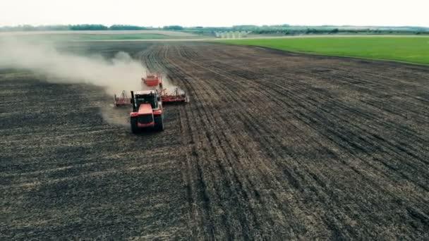 Červené vozidlo dělá rýhy pro semena na zemědělské půdě, pohled shora.