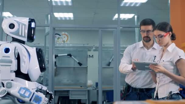 Man and woman check robots work.