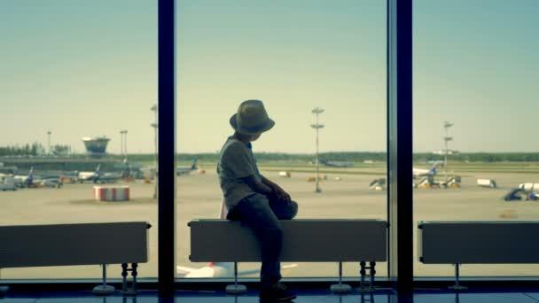 Dítě sedí a dívá na letadla.