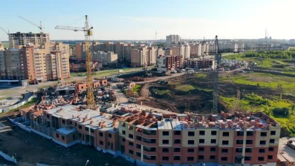 Proces budování na staveništi. Jeřáby stavět nové domy na okraji města