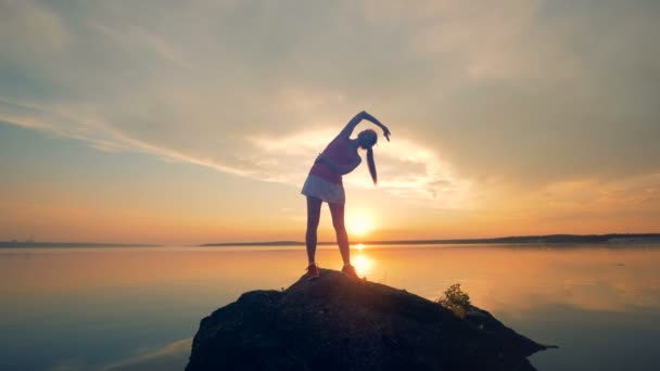 Sportswoman warms up on a rock near lake. A girl stretches her body before running on a sunset background.
