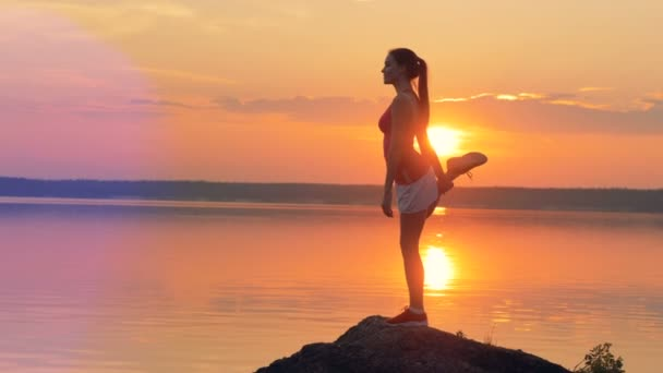 Female jogger takes yoga pose near lake.