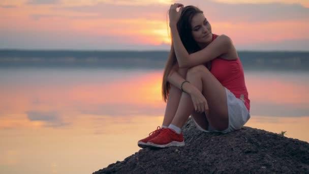 Jeden dívky sedí poblíž jezera po tréninku, zblízka.