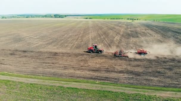 Plowing tractor rides on a big field, top view.