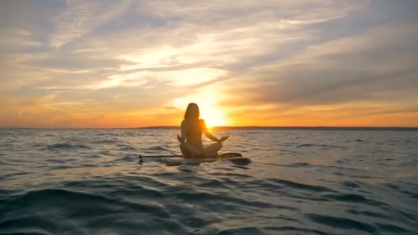 Meditation process on a surfboard. Female surfer meditates on her board while floating on water.