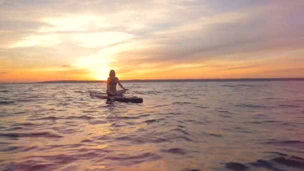 A girl meditating on water in the evening. Female surfer sits on her board in the ocean, practicing yoga.