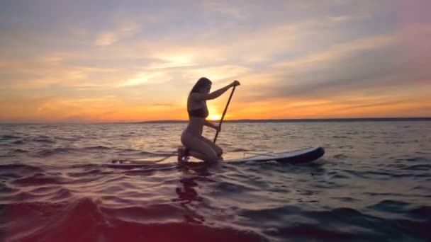 A woman rows on a sunset background, side view. A girl rides her surfing board, going in the ocean.