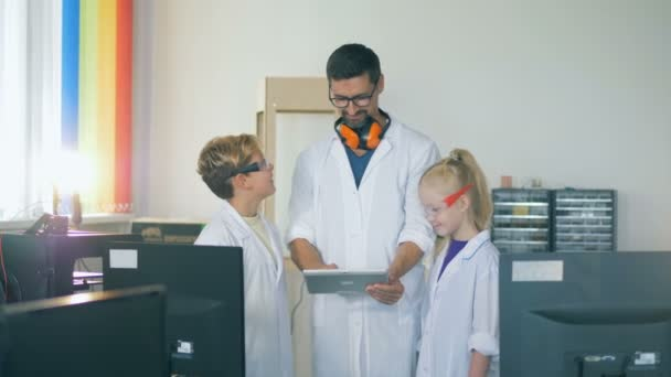 A teacher and kids in a school laboratory room study technology.