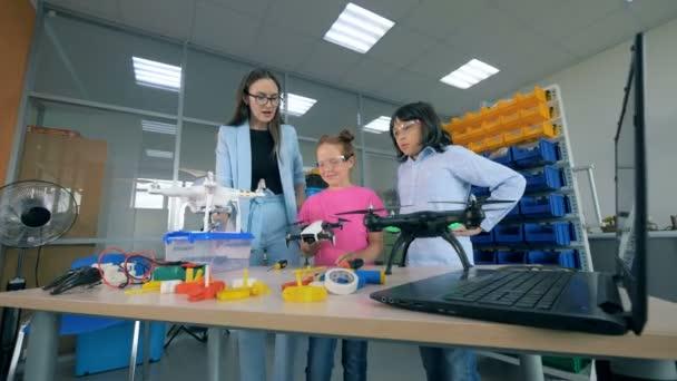 Lehrer erklären Kindern, wie Drohnenkopter, Fluggeräte funktionieren. 4k.