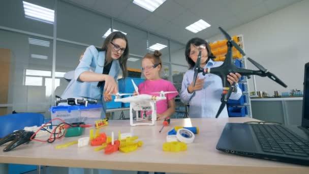 Lehrerinnen studieren innovative Technologien - Drohnen, Flugzeuge in der Grundschule. Modernes Bildungskonzept.
