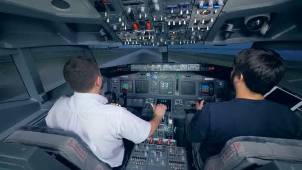 Zwei Männer üben Landung in einer Flugsimulationsmaschine