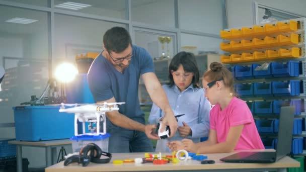 Schüler erkunden Drohne, Copter und Flugzeug mit einem Lehrer im Technikunterricht.