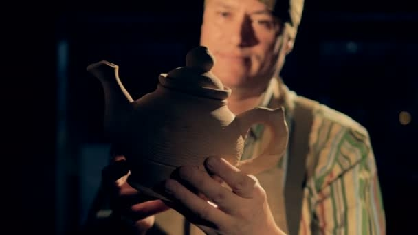 A craftsman at a pottery checks a clay kettle, then looks at a camera.