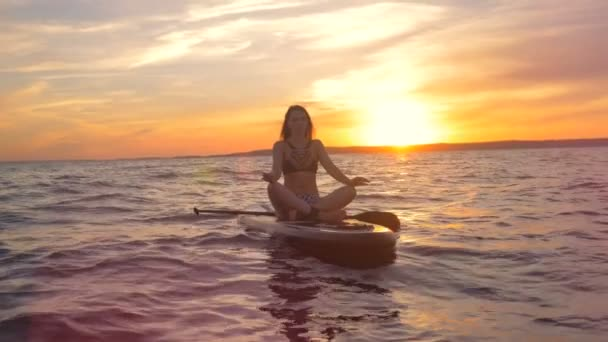 Gorgeous woman is sitting in a lotus pose on a board during sunset practicing yoga.