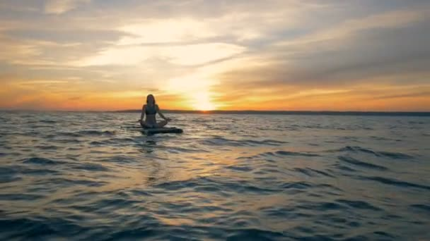 Scenic sunset at sea and a graceful lady floating across it on a board
