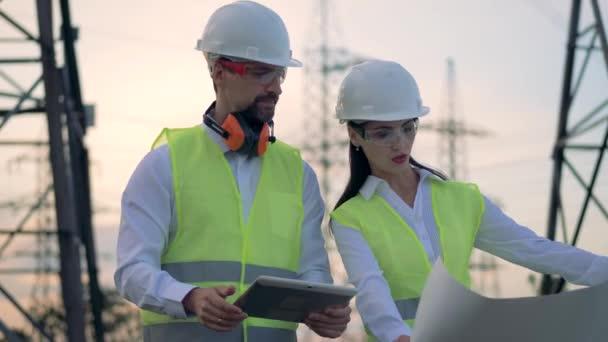 Samec a samice inženýři v přilbu diskutovat o projektu výstavby při prohlídce rozvodny energie