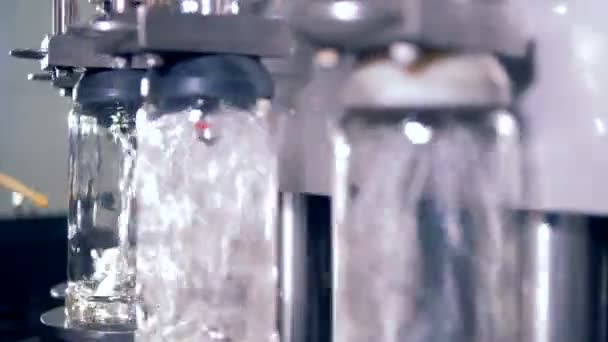 Metal machine pours alcohol into bottles, close up.