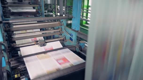 Machine works in printing office, close up. Newspaper printing equipment working.