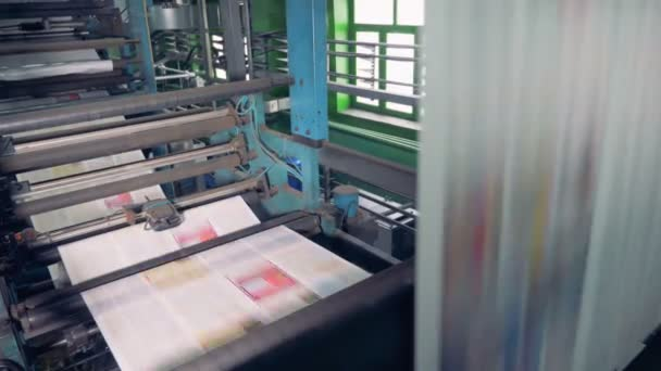 Colored papers on a printing machine. Newspaper printing equipment working.