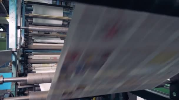 Rolling machine in a print office, close up. Newspaper printed on a printing house machine.