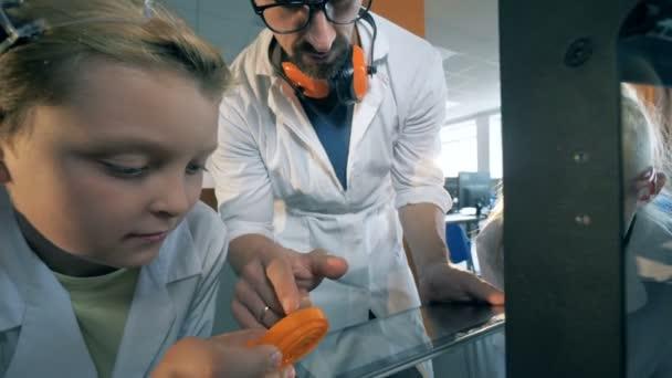 Kinder beobachten genau ein Detail gedruckt in 3d mit einem Labor-Lehrer