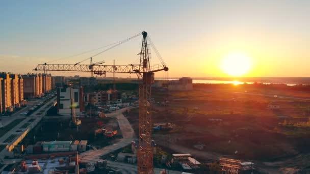 Technické zařízení budov je na staveništi. Stavební jeřáb při západu slunce pozadí
