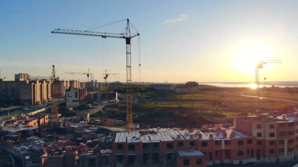 Stavební jeřáby postavit velký dům na předměstí. 4k.