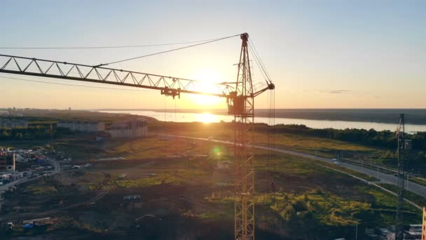 Žlutý jeřáb při západu slunce, zblízka. Věžový jeřáb na staveništi.