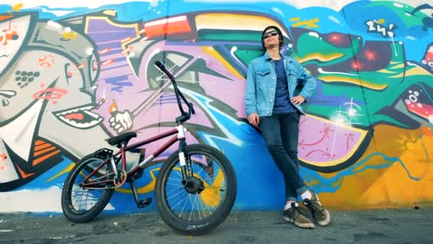 Muž cyklista je opřený o graffiti zeď s jeho kolo to klidna a bezpecna
