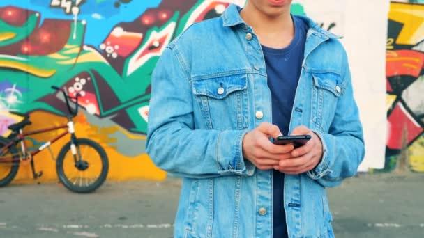 A mobil telefon a graffiti fal közelében áll tinédzser egy farmer dzseki