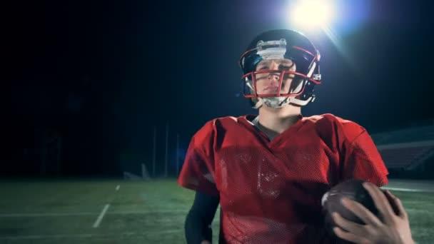 Muž chodí, v rukou držel míč na americký fotbal. 4k.