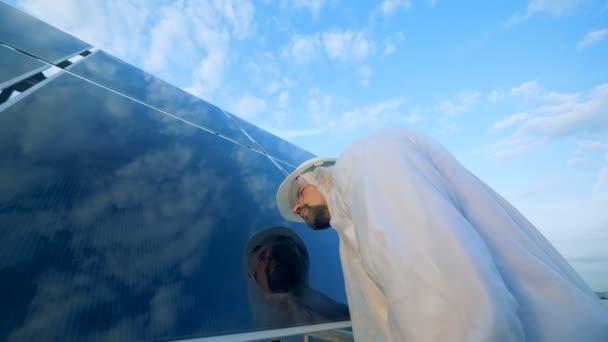 Muž kontroluje sluneční panely na střeše. Moderní inovativní průmysl koncept
