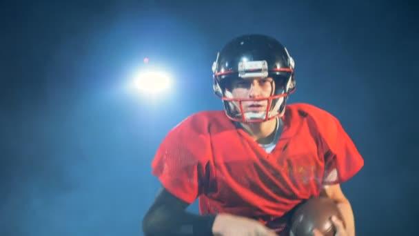 Americký fotbal hráč běží na světlém pozadí, zblízka.