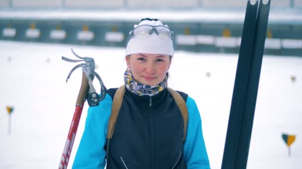 Female biathlete looking at a camera, close up.