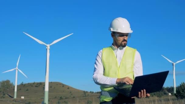 Grünes Energiekonzept. Ein Mann schaut sich Windräder an und tippt auf seinem Laptop. 4k