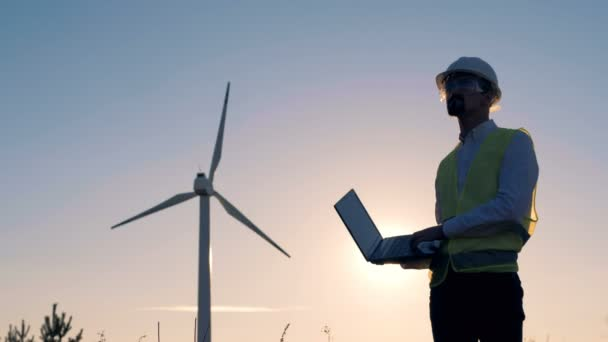 Male engineer holds a laptop, types on it and checks electric windmills   Renewable electririty, green energy concept