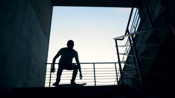 A person jumps on his board in a staircase and fails. Slow motion.