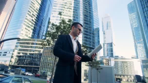 Obchodní komplex z mrakodrapů se mladý muž podnikatel stojící vedle něj. 4k