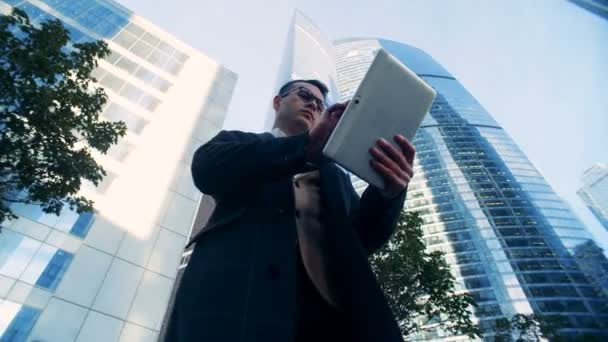 Male successful financial expert surrounded by urban buildings, skyscrapers. Red epic cinema camera shot.