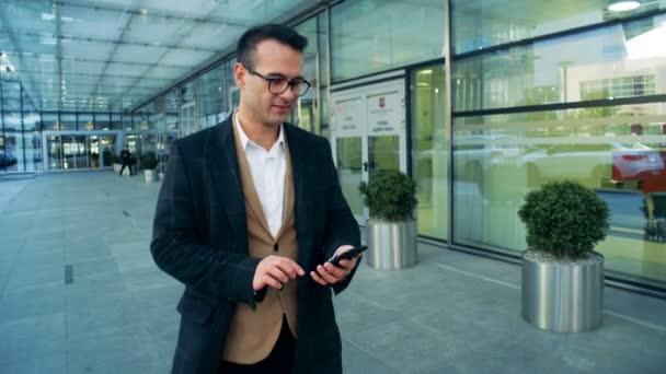 Mužské office manager je pěší podél budovy a provozu smartphone s úsměvem. 4k